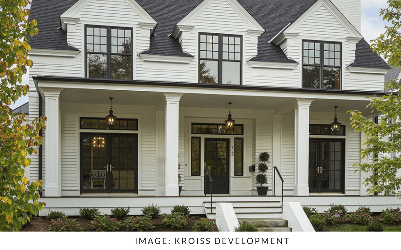 White Home Exterior with black windows and covered front porch.