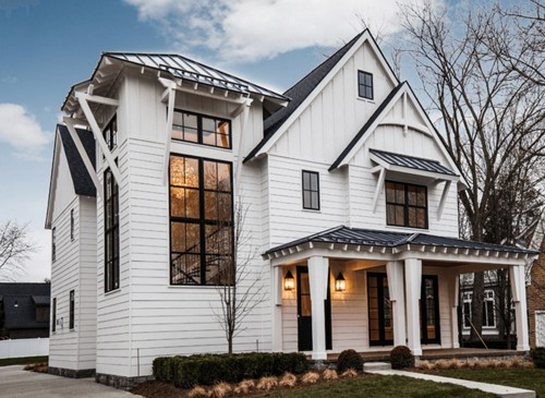 White home exterior with black windows and black metal roof.