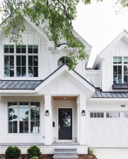 Gorgeous white home exterior with black metal roof.