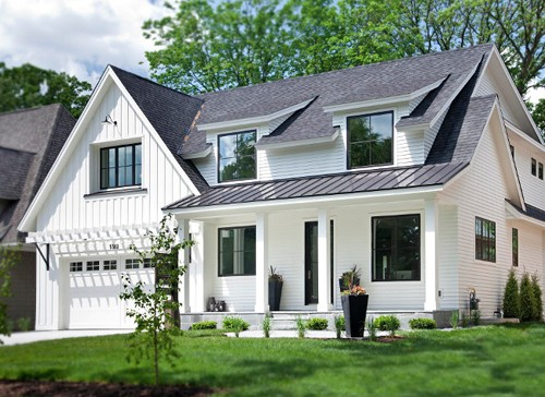 White home exterior with front load garage and black roof.