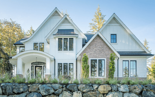 White home exterior with brick and arched entry.
