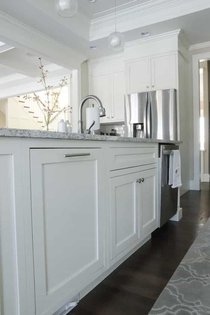 Tips for designing a functional kitchen pull out garbage can. white kitchen island with sink and dishwasher.