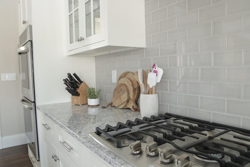 tips for designing a functional kitchen dishes. white kitchen with grey subway tile backsplash and quartz counters.