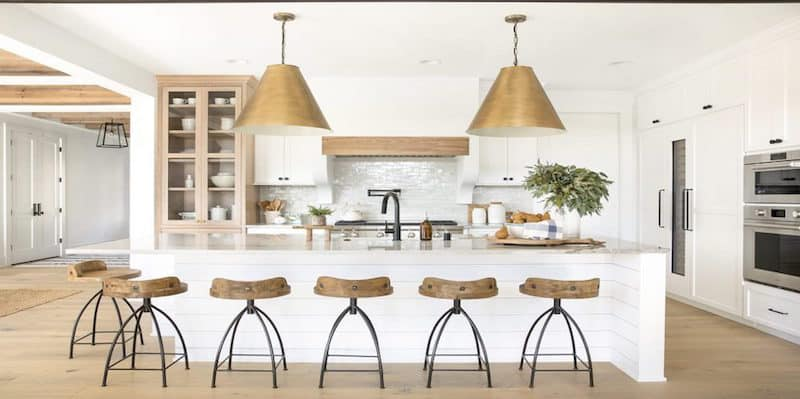 White kitchen with wood accents and large gold island pendants.