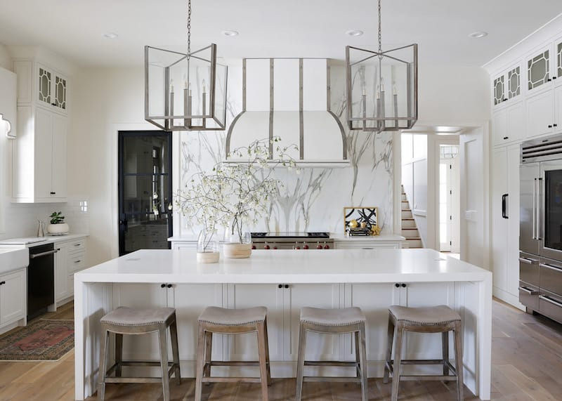 White and marble kitchen with two large silver pendants