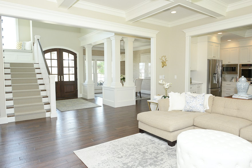 open layout of neutral home with lots of trim work and wood floors
